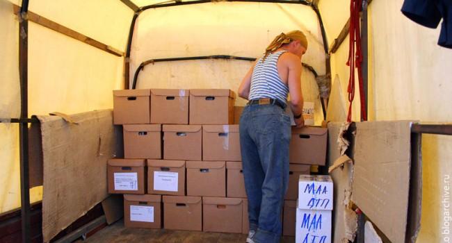 Грузчик укладывает коробки для переезда в кузов Газели