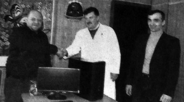 В. Э. Поляков вручает новый компьютер.